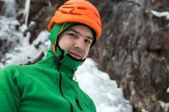 Mann im orange Sturzhelm, der uns auf Felsen- und Eishintergrund betrachtet Stockfoto