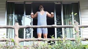 Mann im Retro- Badeanzug bildet auf dem Balkon aus stock video footage