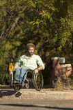 Mann im Rollstuhl an der Stadt-Beschränkung Stockfotografie