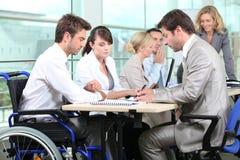 Mann im Rollstuhl mit Kollegen Stockbilder