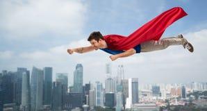 Mann im roten Superheldkapfliegen in einer Luft über Stadt lizenzfreie stockbilder