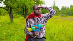 Mann im roten Umhang, der mit Spielzeugpistole auf dem fie zielt und schießt stock footage