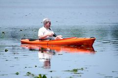 Mann im Ruhestand, der in einen Kajak schwimmt lizenzfreies stockfoto