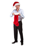 Mann im Sankt-Hut entsetzt am Weihnachtsstrumpf stockbild