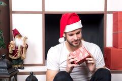 Mann im Sankt-Hutblick auf roten Kasten am Kamin Stockfotografie