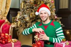 Mann im Sankt-Hutlächeln mit Geschenken am Weihnachtsbaum Lizenzfreie Stockfotografie