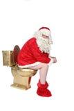 Mann im Sankt-Kostüm, das auf einer goldenen Toilette sitzt Lizenzfreies Stockfoto