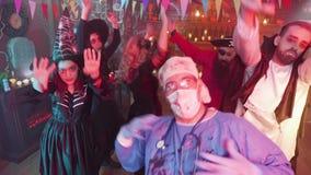 Mann im schlechten Doktorkostümtanzen mitten in einer Gruppe Freunden, die Halloween feiern stock footage