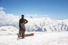 Mann im Schnee mit Schlitten stockfotografie