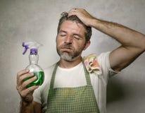 Mann im Schutzblech mit Küchenstoff und reinigendem Spraygefühl überwältigt und gebohrt, inländische Hausarbeit des Säuberns und  stockfoto