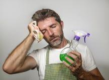 Mann im Schutzblechholding-K?chenstoff und im reinigenden Spraygef?hl ?berw?ltigt und gebohrt, inl?ndische Hausarbeit des S?ubern stockfotos