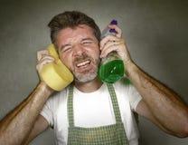 Mann im Schutzblechholdingschwamm- und -reinigungsmittelspraygef?hl ?berw?ltigt und gebohrt, inl?ndische Hausarbeit des S?uberns  lizenzfreie stockfotografie
