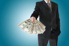 Mann im schwarzen Anzug bietet das Geld an, das auf blauem Hintergrund lokalisiert wird Stockfotografie