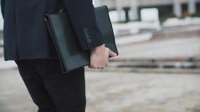 Mann im schwarzen Anzug geht mit einem Ordner stock footage
