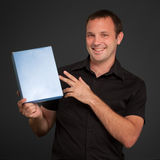 Mann im Schwarzen, das ein unbelegtes Paket darstellt Lizenzfreies Stockbild