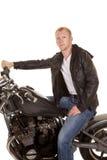Mann im schwarzen Jackenmotorrad an Hand auf dem Lenkstangenschauen Lizenzfreies Stockbild