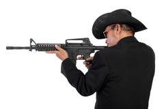 Mann im schwarzen Schießen mit Gewehr Stockbilder