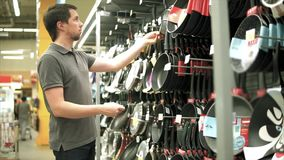 Mann im Shop, der Gerät wählt Er Küchentopf in die Hand nehmend stock footage