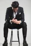 Mann im Smoking, das unten schaut, beim Sitzen auf einem Schemel, Stockfotos