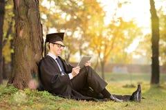 Mann im Staffelungskleid, das an einer Tablette im Park arbeitet Lizenzfreie Stockfotos