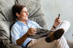 Mann im Stuhl, der mit Handy simst Stockbild
