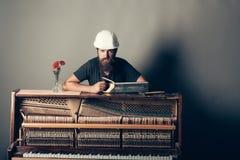 Mann im Sturzhelm nahe Klavier mit sah und Hammer Stockbild