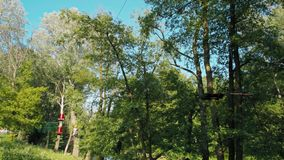 Mann im Sturzhelm schiebt hinunter ZipLine Abenteuer-im hohen Seil-Park im Sommer stock video