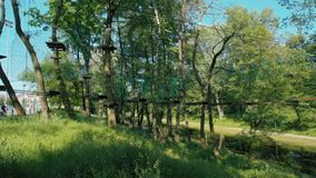 Mann im Sturzhelm schiebt hinunter Ziplinie Abenteuer-im hohen Seil-Park im Sommer stock video footage