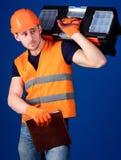 Mann im Sturzhelm, Schutzhelm hält Werkzeugkasten und Ordner mit Dokumenten, blauen Hintergrund Arbeitskraft, Reparaturhauer, Sch Stockfotos