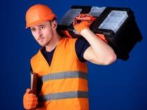 Mann im Sturzhelm, Schutzhelm hält Werkzeugkasten und Ordner mit Dokumenten, blauen Hintergrund Reparieren Sie Servicekonzept sch Stockbild