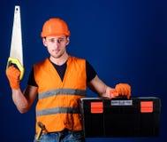 Mann im Sturzhelm, Schutzhelm trägt Werkzeugkasten und hält Handsaw, blauen Hintergrund Arbeitskraft, Reparaturhauer, Schlosser a Lizenzfreie Stockfotos
