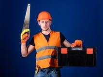 Mann im Sturzhelm, Schutzhelm trägt Werkzeugkasten und hält Handsaw, blauen Hintergrund Tischlerkonzept Arbeitskraft, Reparaturha Stockfoto