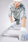 Mann im Sturzhelm und Handschuhe, die Leiter klettern Lizenzfreie Stockfotografie