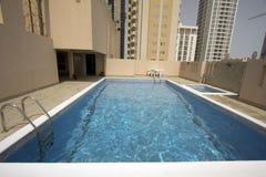 Mann im Swimmingpool am Dach Stockbild