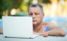 Mann im Swimmingpool mit Laptop und Getränk Stockbild