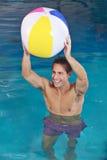 Mann im Swimmingpool mit Wasserball Stockbilder