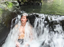 Mann im thermischen Wasserfall lizenzfreies stockfoto