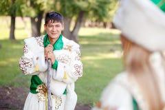 Mann im traditionellen festlichen Kleid von Steppennomaden, gelehnt auf seinem Stock, Frau betrachtend Stockbild