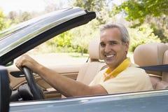 Mann im umwandelbaren Autolächeln Stockfoto