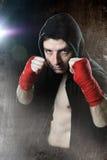 Mann im Verpacken Hoodiepullover mit Haube auf Kopf mit den eingewickelten Handhandgelenken bereit zu kämpfen Stockfoto
