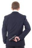 Mann im versteckenden Gewehr des Anzugs hinter seinem zurück lokalisiert auf Whit Lizenzfreies Stockfoto