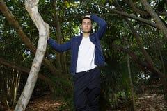 Mann im Wald, der mit der Hand auf Haar aufwirft Lizenzfreies Stockbild
