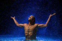 Mann im Wasser unter Regen Lizenzfreies Stockbild