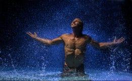 Mann im Wasser unter Regen Lizenzfreie Stockbilder