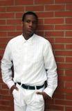 Mann im Weiß durch Backsteinmauer Stockfotografie