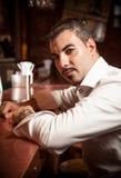 Mann im weißen Hemd, das nahe Stangenschreibtisch sitzt stockfotos