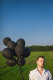 Mann im weißen Hemd mit schwarzen Ballonen auf dem Gebiet Stockbild