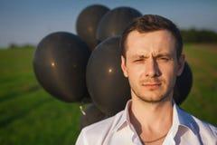Mann im weißen Hemd mit schwarzen Ballonen auf dem Gebiet Lizenzfreies Stockfoto