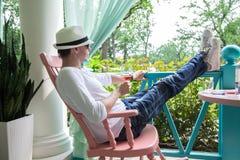 Mann im weißen Hut und im Glas Wein stillstehend auf Terrasse Lizenzfreie Stockfotografie