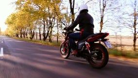 Mann im weißen Sturzhelmreitmotorrad auf Landstraße bei Herbstsonnenuntergang stock footage